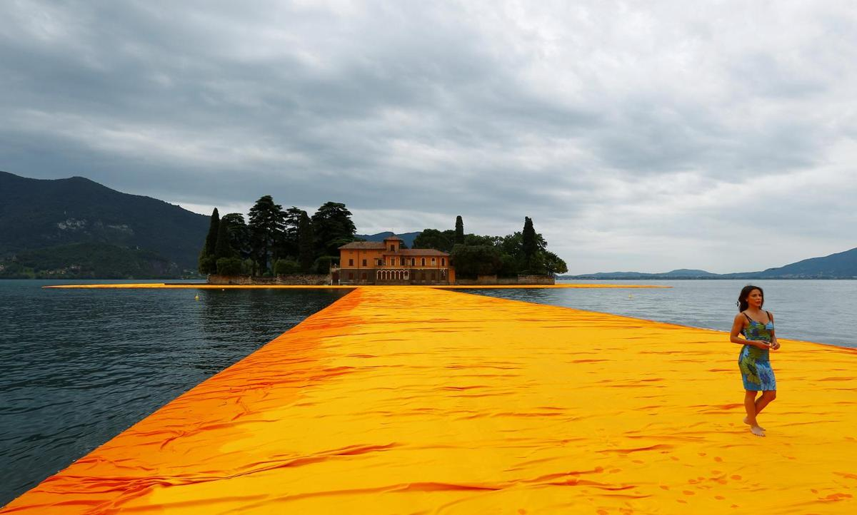 A woman walks on the installation 'The Floating Piers' by Bulgarian-born artist Christo Vladimirov Yavachev known as Christo, on the Lake Iseo, northern Italy, June 16, 2016.REUTERS/Stefano Rellandini FOR EDITORIAL USE ONLY. NO RESALES. NO ARCHIVES.